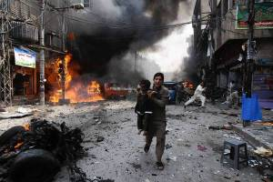 A man and a child flee the site of a blast in Peshawar, Pakistan