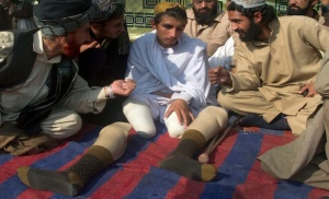 Tribesmen sit with Khan, who says he lost both legs and one eye in a drone strike on his house last year, as they demonstrate in Islamabad