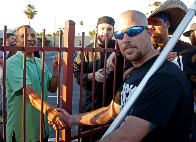 Jon Ritzheimer, right, talks to a member of the board, Muhammad Alrokh, left, outside the Islamic Community Center of Phoenix, Friday, May 29, 2015. About 500 protesters gathered outside the Phoenix mosque on Friday as police kept two groups sparring about Islam far apart from each other.  (AP Photo/Rick Scuteri)