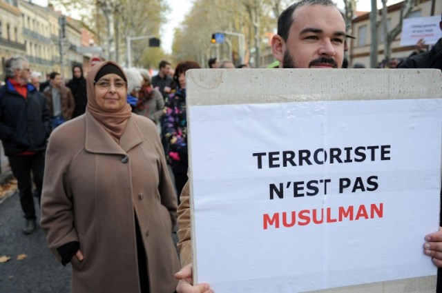 "A man holds a placard reading ""Terrorist is not Muslim"" as people take part in a silent walk to support freedom and peace and against barbarism, and misconceptions in Toulouse on November 21, 2015, following Paris' November 13 terror attacks. More than 10,000 people marched today in the French city of Toulouse for peace and against ""barbarity"" a week after the devastating attacks in the capital left 130 people dead. The march took place largely in silence. AFP PHOTO / REMY GABALDA / AFP / REMY GABALDA"