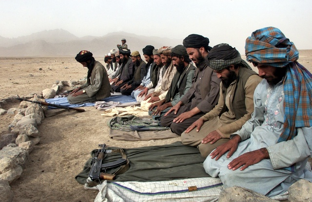 Taliban fighters pray in the outskirts of the city of Kandahar, Afghanistan in this November 3, 2001 file photo. Almost five years after thousands of Taliban fighters fled Afghanistan to escape a U.S.-led invasion, Pakistan is still unable to shake off suspicions that it is allowing them to operate from its soil. REUTERS/Mian Khursheed/Files (PAKISTAN)