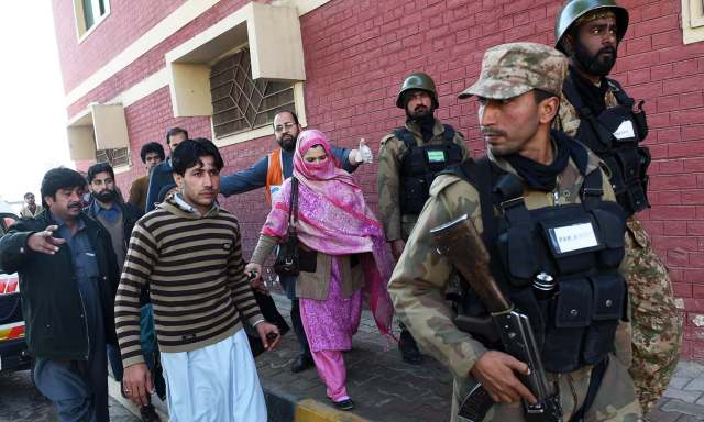 Pakistani army soldiers rescue people from Bacha Khan university following an attack by militants in Charsadda, about 50 kilometres from Peshawar, on January 20, 2016. At least 21 people died in an armed assault on a university in Pakistan on January 20, where witnesses reported two large explosions as security forces moved in under dense fog to halt the bloodshed. AFP PHOTO / A MAJEED