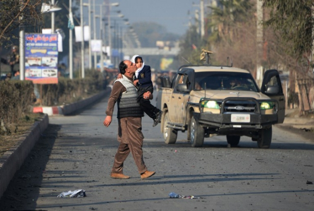 An Afghan man kisses his daughter as he walks near an attack from a building close to the Pakistan consulate in Jalalabad on January 13, 2016. A suicide bombing followed by gunfire rocked an area near the Pakistani consulate in the eastern Afghan city of Jalalabad on January 13, killing at least two police officers, officials said. AFP PHOTO / Noorullah Shirzada / AFP / Noorullah Shirzada