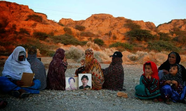 In this Tuesday, Nov. 19, 2013, photo, Pakistani families rest next to photographs of their relatives, who were allegedly abducted by Pakistani security forces, as they march toward Karachi, in Gadani, Pakistan. Baluch is one of roughly two dozen activists making the journey on foot from Quetta, the capital of southwest Baluchistan province, to the southern port city of Karachi to protest thousands of people who have gone missing over the years as Pakistani authorities have battled a separatist insurgency in Baluchistan. (AP Photo/Shakil Adil)